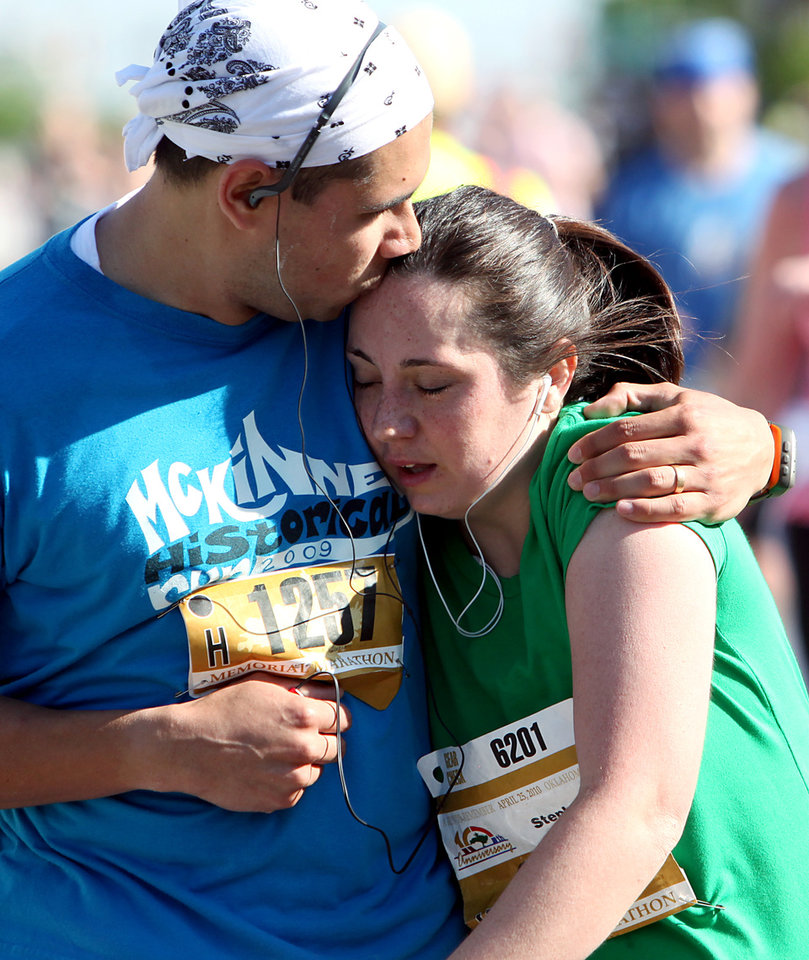 Photo - B.J. GARCIA: B.J. and Stephanie Garcia embrace as they finish the half marathon during the Tenth Annual Oklahoma City Memorial Marathon in Oklahoma City on Sunday, April 25, 2010. By John Clanton, The Oklahoman ORG XMIT: KOD