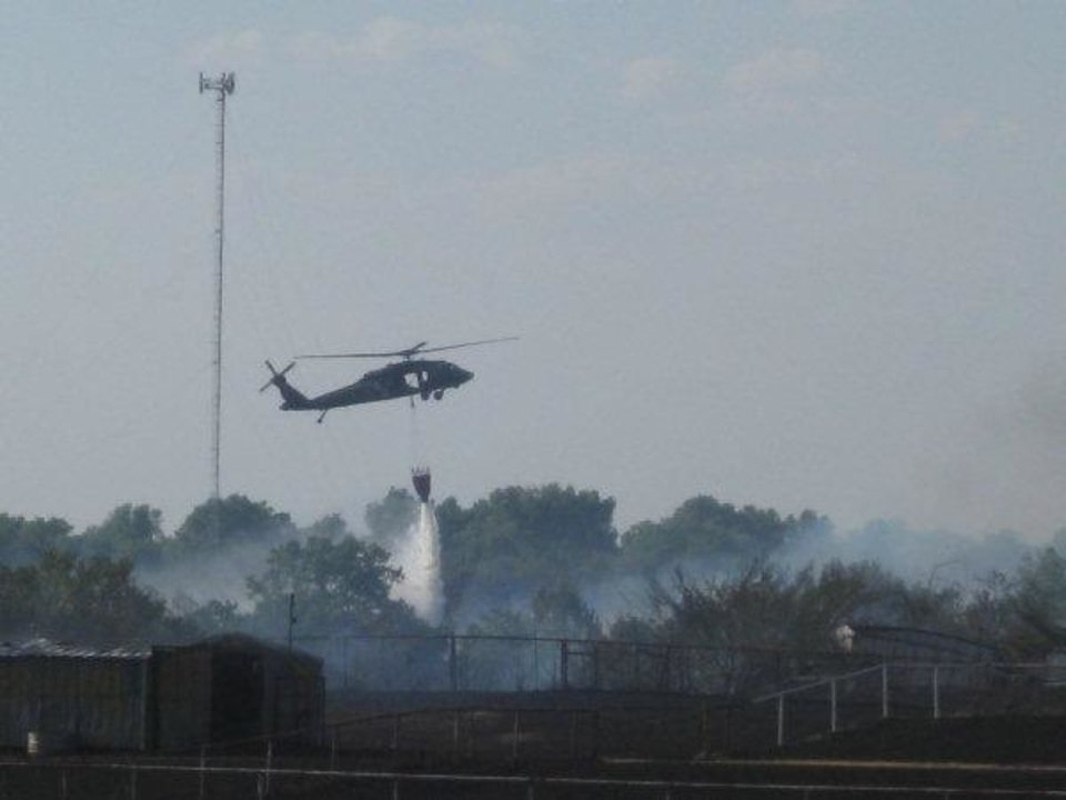 Photo - An Army National Guard helicopter drops water on the wildfire near SW 119 and Mustang Road Monday afternoon.  MATT DINGER - MATT DINGER