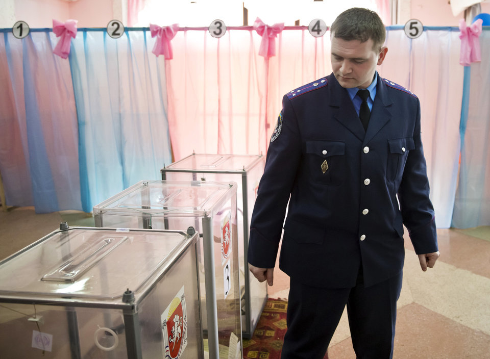 Photo - A Ukrainian policeman looks at ballot boxes after casting his vote in Perevalne, Ukraine, Sunday, March 16, 2014. Residents of Ukraine's Crimea region are voting in a contentious referendum on whether to split off and seek annexation by Russia. (AP Photo/Vadim Ghirda)