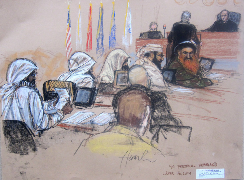 Photo - In this Pentagon-approved sketch by court artist Janet Hamlin,  the Sept. 11 accused co-conspirators attend a pretrial hearing the Guantanamo Bay U.S. Naval Base in Cuba, Monday, June 16, 2014. Defense council James Herrington is at podium addressing presiding Judge James Pohl. The accused, right to left: Khalid Sheikh Mohmmad, Walid bin Attash, Ramzi bin al shibh, Aziz Ali, Mustafa al Hawsawi.  Lawyers for Guantanamo prisoners charged in the Sept. 11 attack say the FBI has questioned more people who work as support staff on their legal teams than previously disclosed, a development that may prompt a new detour in an already snarled case as the war crimes tribunal reconvened Monday at this U.S. base.  (AP Photo/Janet Hamlin, Pool)