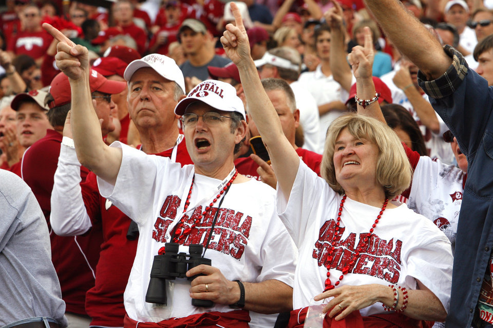 Photo - Loyd Thayer and Ann Cosgrove cheer the Sooners at the college football game between the University of Oklahoma Sooners (OU) and the University of Cincinnati Bearcats (UC) at Paul Brown Stadium on Saturday, Sept. 25, 2010, in Cincinnati, Ohio.   Photo by Steve Sisney, The Oklahoman