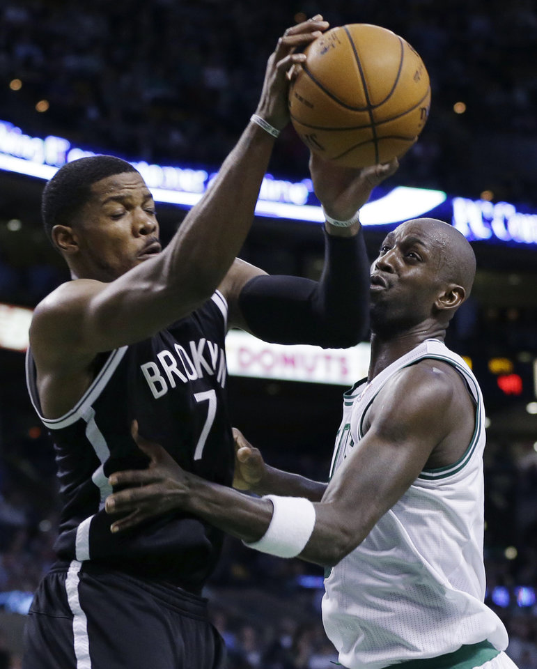Photo - Brooklyn Nets guard Joe Johnson (7) brings down a rebound against Boston Celtics center Kevin Garnett during the second quarter of an NBA basketball game in Boston, Wednesday, April 10, 2013. (AP Photo/Elise Amendola)