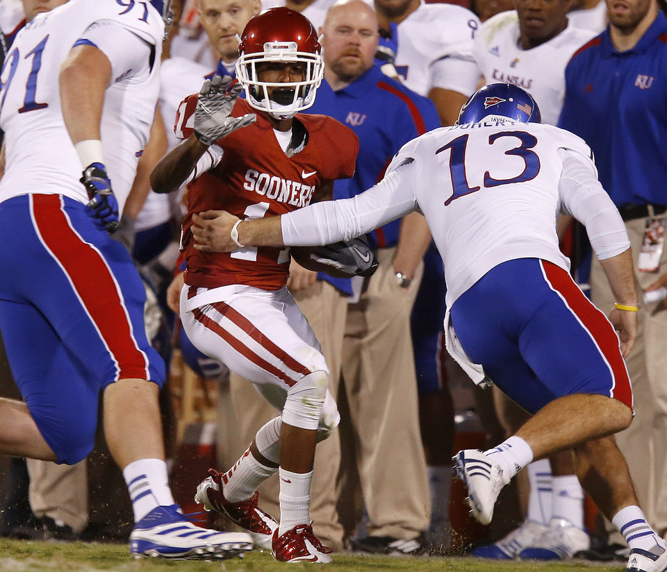 Photo - OU's Jalen Saunders (14) tries to get past KU's Ron Doherty (13) during the college football game between the University of Oklahoma Sooners (OU) and the Kansas Jayhawks (KU) at Gaylord Family-Oklahoma Memorial Stadium in Norman, Okla., Saturday, Oct. 20, 2012. Photo by Bryan Terry, The Oklahoman