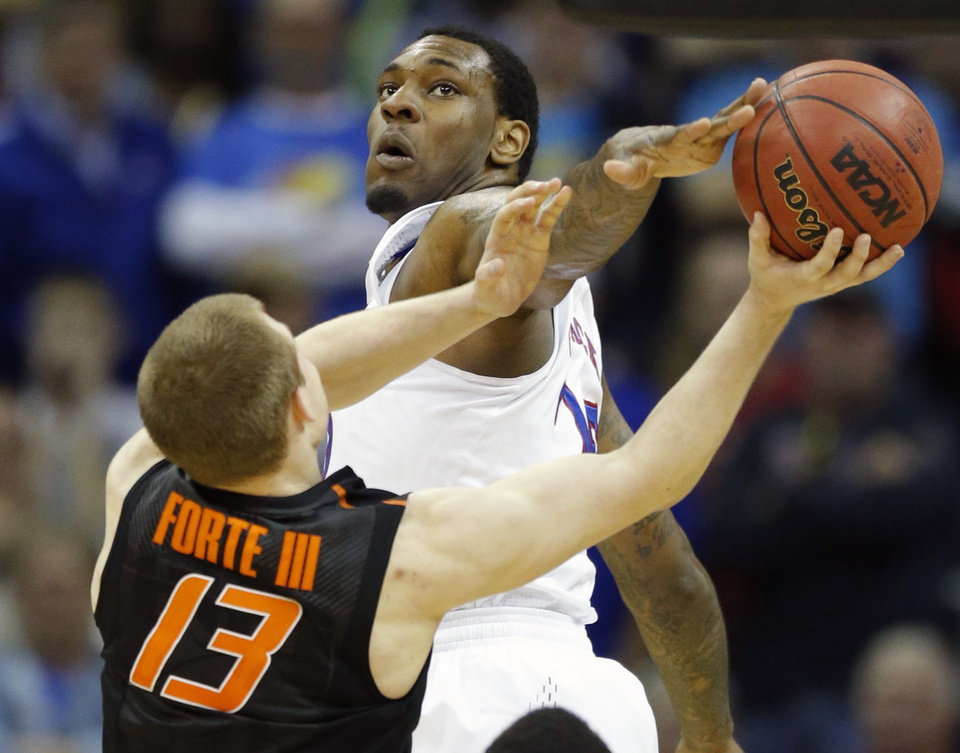 Photo - Kansas forward Tarik Black, top, blocks a shot by Oklahoma State guard Phil Forte III (13) during the second half of an NCAA college basketball game in the quarterfinals of the Big 12 Conference men's tournament in Kansas City, Mo., Thursday, March 13, 2014. Kansas defeated Oklahoma State 77-70 in overtime. (AP Photo/Orlin Wagner)