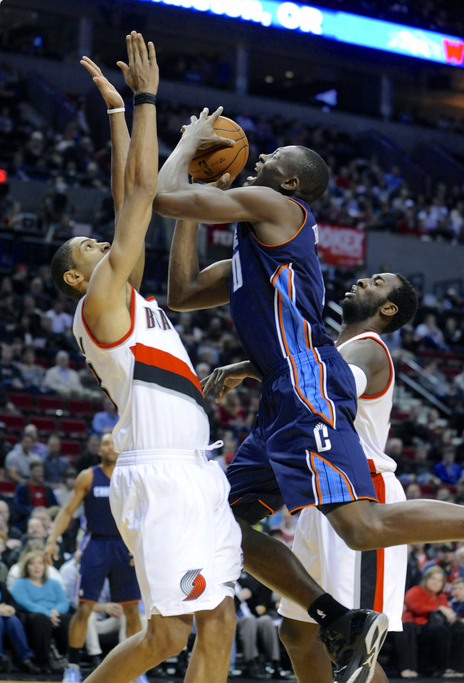 Photo - Charlotte Bobcats' Bismack Biyombo (0) shoots against Portland Trail Blazers' Nicolas Batum (88) and JJ Hickson (21) during the first half of an NBA  basketball game in Portland, Ore., Monday, March 4, 2013. (AP Photo/Greg Wahl-Stephens)