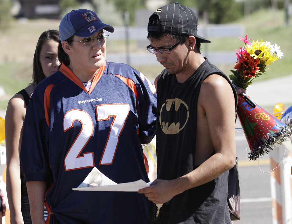 Photo -   Shelly Fradkin, left, and Isaac Pacheo, right, cry as they look at photos of their friend Alex Sullivan, Saturday, July 21, 2012, as they visit a memorial near the movie theater in Aurora, Colo. Twelve people were killed and dozens were injured in the attack early Friday at the packed theater during a showing of the Batman movie,