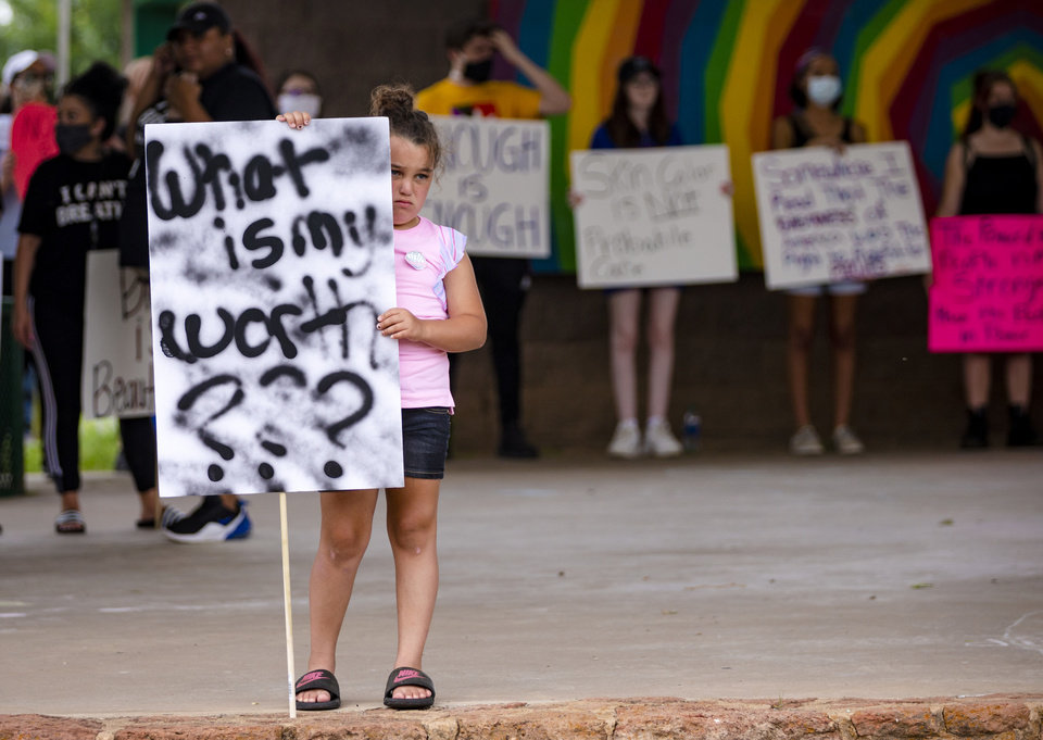 Photo - Bailey Golden, 8, carries a sign as she gathers with other protesters during a protest at Andrews Park on Monday, June 1, 2020, in Norman, Okla. in response to the death of George Floyd.  [Chris Landsberger/The Oklahoman]