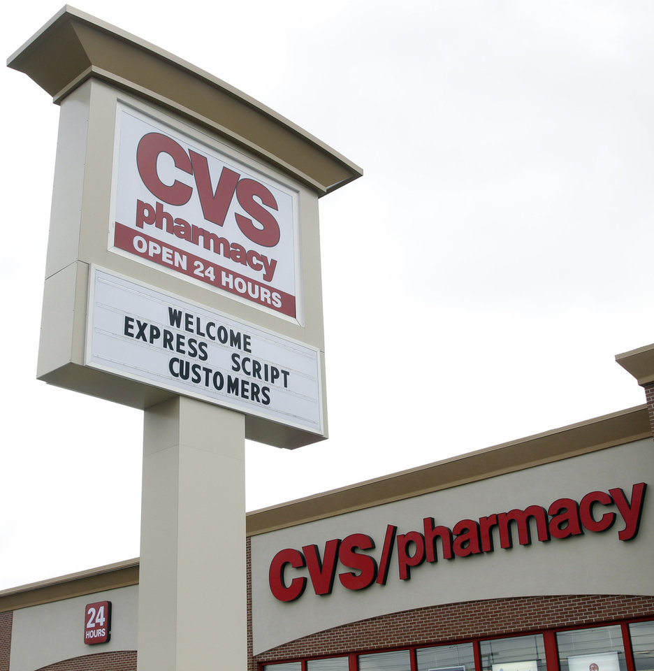 Photo -   A sign at a CVS Pharmacy welcomes Express Script Customers on its sign at a store in Indianapolis, Wednesday, Feb. 8, 2012. CVS Caremark says its fourth-quarter earnings climbed nearly 4 percent, as the drugstore operator's pharmacy services revenue swelled because of a long-term contract and new business. (AP Photo/Michael Conroy)