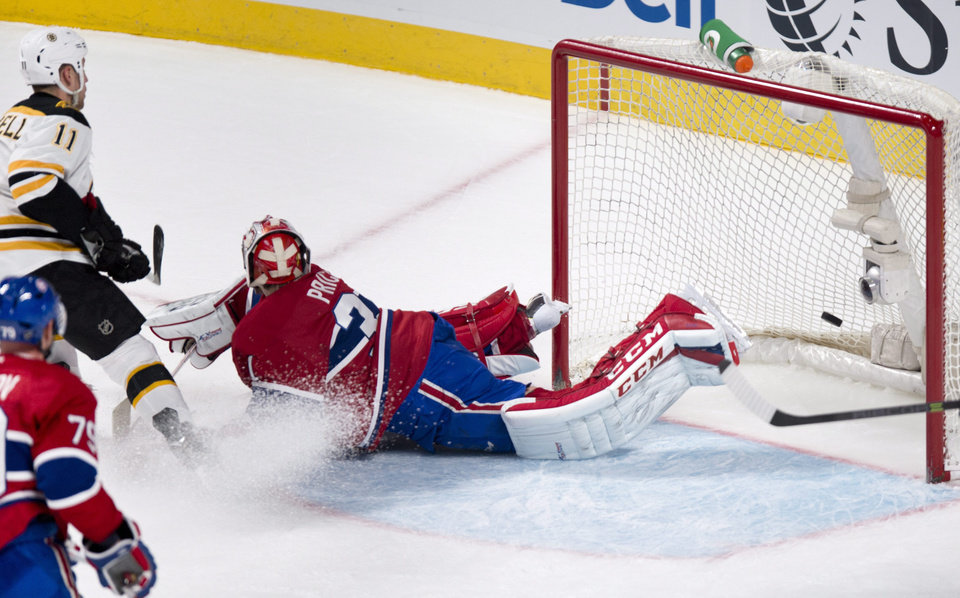 Photo - Boston Bruins' Gregory Campbell scores past Montreal Canadiens goalie Carey Price during first period NHL hockey action Thursday, Dec. 5, 2013, in Montreal. (AP Photo/The Canadian Press, Paul Chiasson)