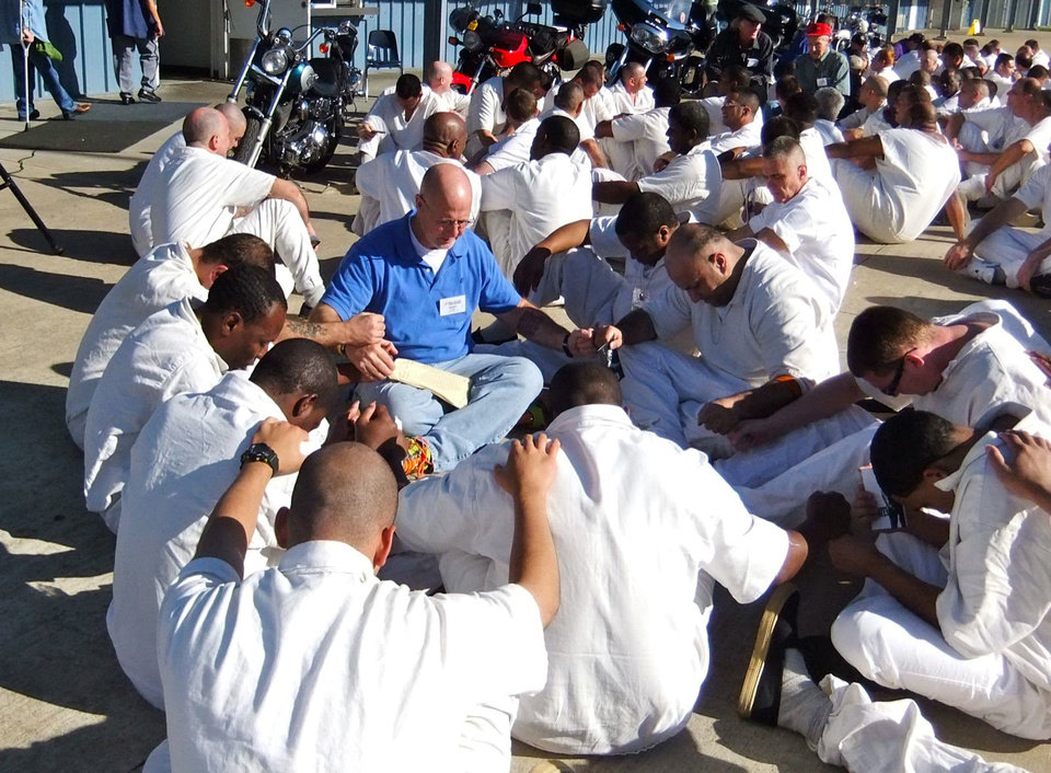 A church volunteer prays with a group of inmates in a prison yard as part of a Bill Glass Weekend of Champions event. Photo provided <strong></strong>