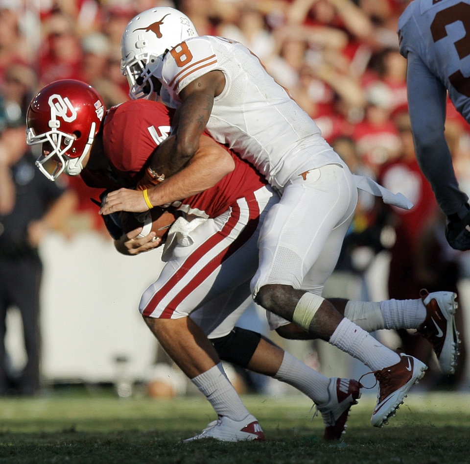 Photo - OU's John Nimmo (5) is tackled by Chykie Brown (8) of Texas during a fake field goal in the foruth quarter of the Red River Rivalry college football game between the University of Oklahoma Sooners (OU) and the University of Texas Longhorns (UT) at the Cotton Bowl on Saturday, Oct. 2, 2010, in Dallas, Texas. OU won, 28-20. Photo by Nate Billings, The Oklahoman