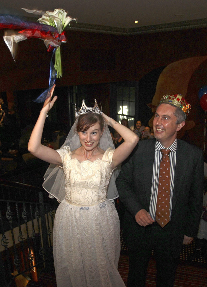 Photo - Dressed as bride and groom, Linzi Aland, center, and Nick Volker, right, do a pretend bouquet  toss during a royal wedding party at the Ancient Britain (the AB) hotel in Sydney, Australia, Friday, April 29, 2011. The hotel is hosting the party during celebrations for the wedding of Prince William and Kate Middleton.(AP Photo/Rob Griffith) ORG XMIT: SYD112