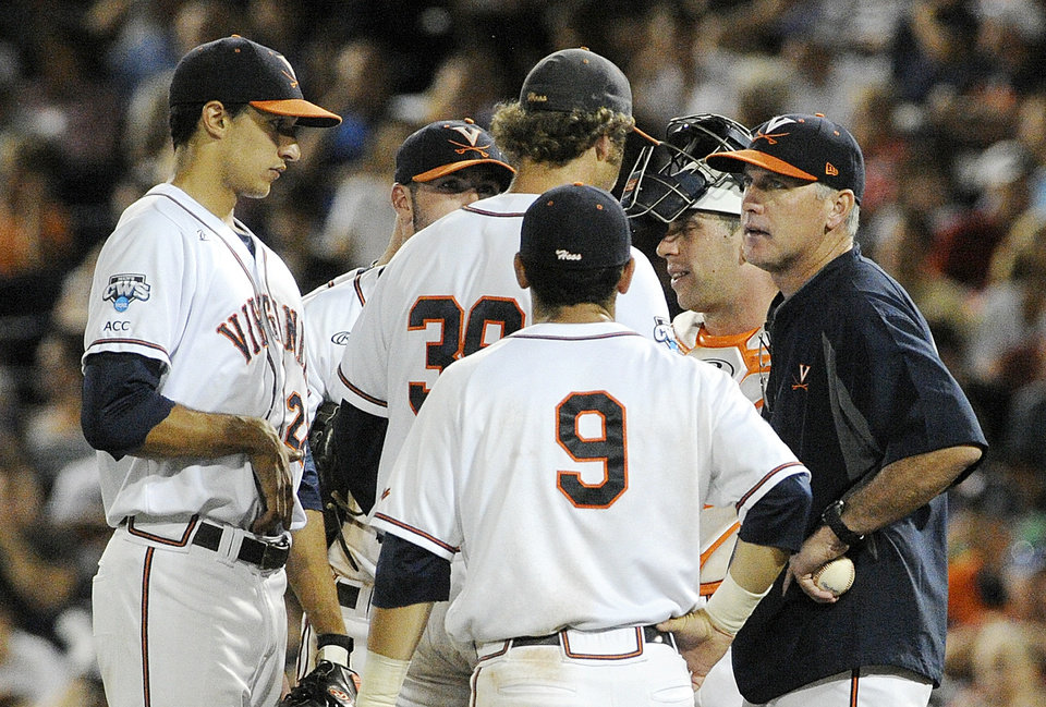 Photo - Virginia coach Brian O'Connor, right, talks to Virginia pitcher Austin Young (39) in the sixth inning of the opening game of the best-of-three NCAA baseball College World Series finals against Vanderbilt in Omaha, Neb., Monday, June 23, 2014. (AP Photo/Eric Francis)