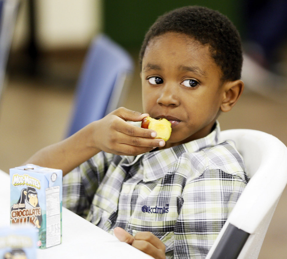 Photo - T.J. O'Neal, 6, eats fruit for a snack as part of Food Day activities at the Salvation Army Boys and Girls Club, 2808 SE 44th St., one of the Regional Food Bank of Oklahoma's Kids Cafe locations, in Oklahoma City, Thursday, Oct. 24, 2013. Photo by Nate Billings, The Oklahoman