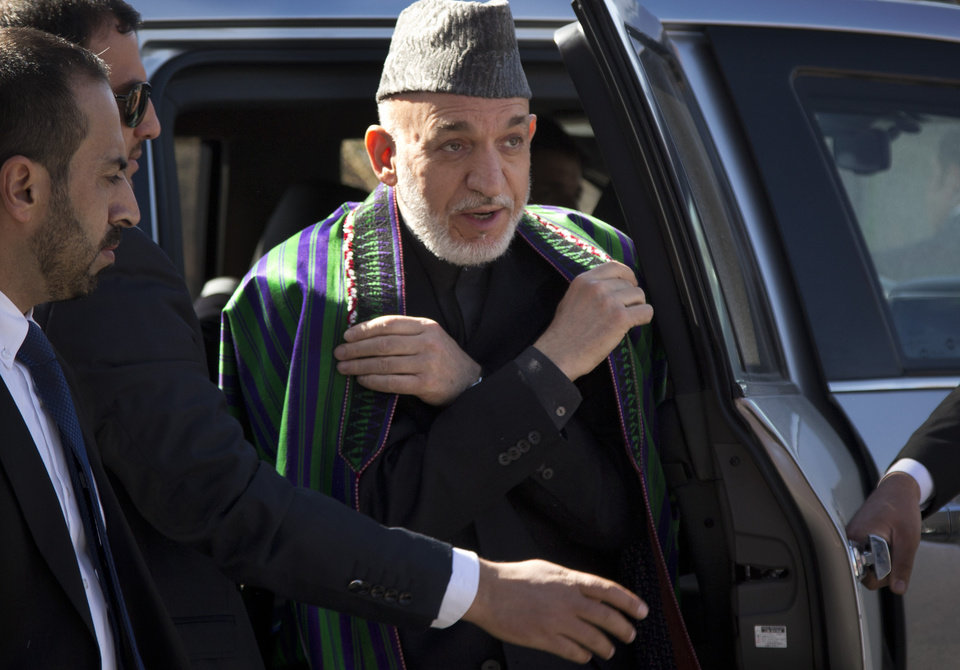 Photo - A Wednesday, March 6, 2013 photo shows Afghan President Hamid Karzai surrounded by his security as he arrives to the Afghan Parliament where he made a speech angering the United States with a promise to release prisoners currently at the U.S. controlled Bagram prison north of Kabul. Karzai has made several statements including accusing the U.S. of colluding with the Taliban, driving relations between the two countries to an all time low. (AP Photo/Anja Niedringhaus)