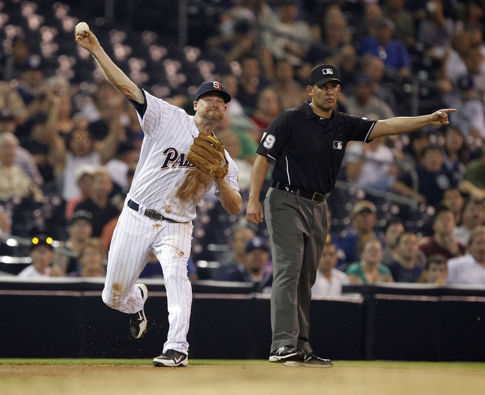 Photo -   San Diego Padres third baseman Chase Headley, left, throws out Colorado Rockies' Wilin Rosario, on a ground ball with third base umpire Manny Gonzalez, right, signals a fair ball during the fourth inning of their baseball game in San Diego, Calif., Friday, Sept. 14, 2012. (AP Photo/Alex Gallardo)