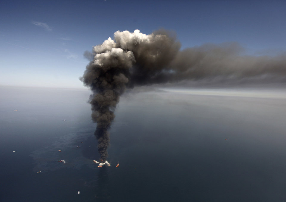 Photo - FILE -  In this Wednesday, April 21, 2010 file photo, oil can be seen in the Gulf of Mexico, more than 50 miles southeast of Venice on Louisiana's tip, as a large plume of smoke rises from fires on BP's Deepwater Horizon offshore oil rig. An April 20, 2010 explosion at the offshore platform killed 11 men, and the subsequent leak released an estimated 172 million gallons of petroleum into the gulf. U.S. District Judge Carl Barbier ruled Thursday, Sept. 4, 2014, in New Orleans, La., that BP acted recklessly and bears most of the responsibility for the oil spill. The ruling exposes BP to about $18 million in civil fines under the Clean Water Act. (AP Photo/Gerald Herbert, File)