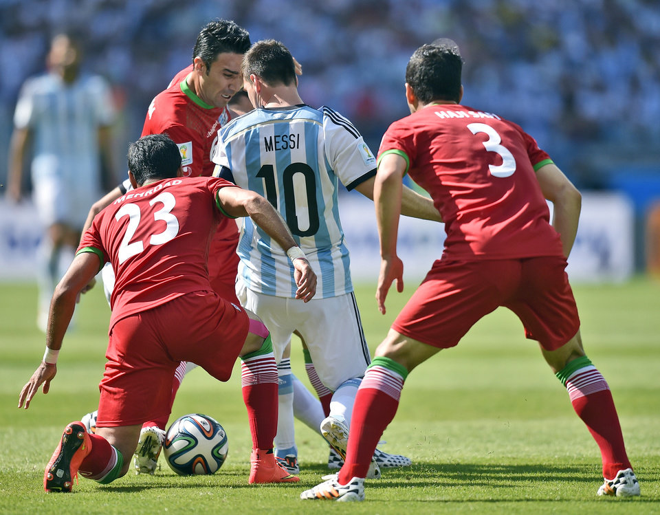 Photo - Argentina's Lionel Messi is boxed in by Iran's Mehrdad Pooladi (23) and Ehsan Haji Safi (3) during the group F World Cup soccer match between Argentina and Iran at the Mineirao Stadium in Belo Horizonte, Brazil, Saturday, June 21, 2014. (AP Photo/Martin Meissner)