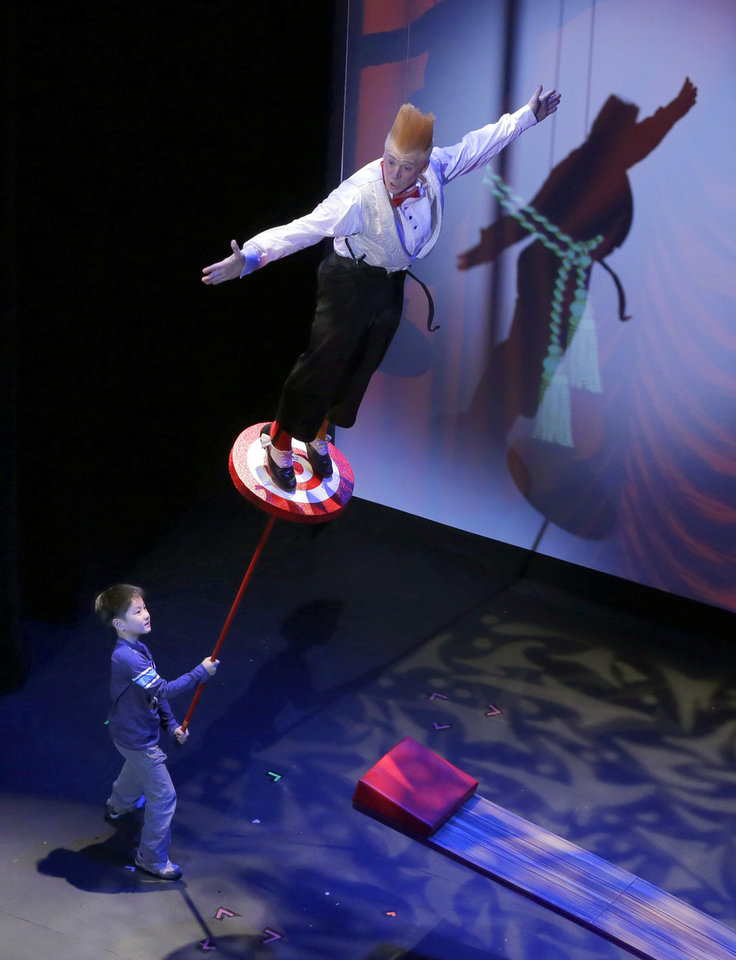 "This March 23, 2013 photo shows Bello Nock, performing a stunt with the assistance of a young audience member, during his ""Bello Mania"" show at the New Victory Theater in New York.  Nock, a seventh-generation circus performer, is never offstage during the 90-minute performance, which combines slapstick clowning with death-defying aerial stunts. He performs through March 31 at the New Victory before moving on to the Canadian side of Niagara Falls and then a 10-week stint at the Beau Rivage Casino in Biloxi, Miss.  (AP Photo/Richard Drew)"