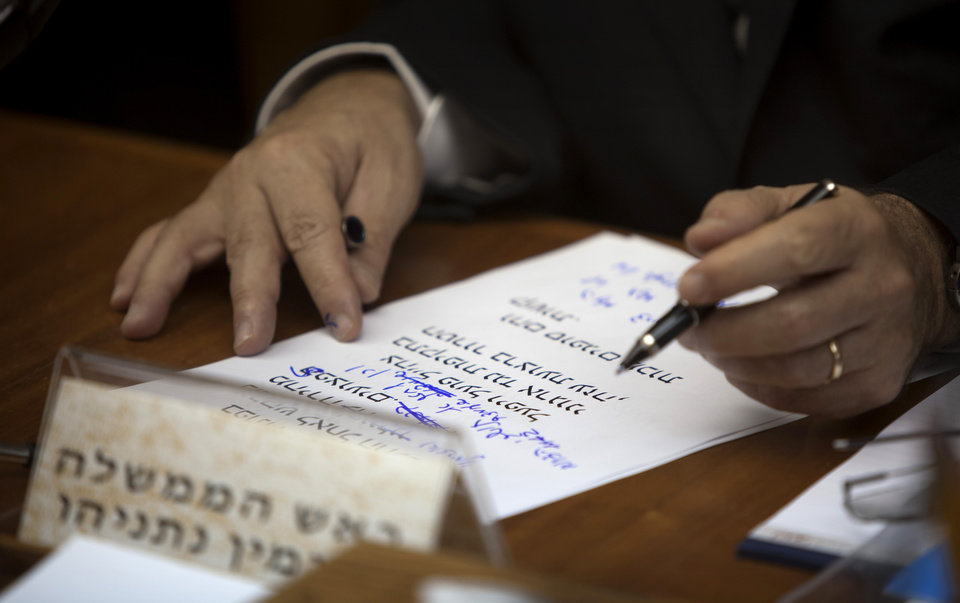 Photo -   Israeli Prime Minister Benjamin Netanyahu adjusts his speech during the weekly cabinet meeting in his Jerusalem office, Sunday, Nov. 11, 2012. Netanyahu says his country is ready to strike harder against Gaza Strip militants if they don't stop attacking Israel. Hebrew reads: