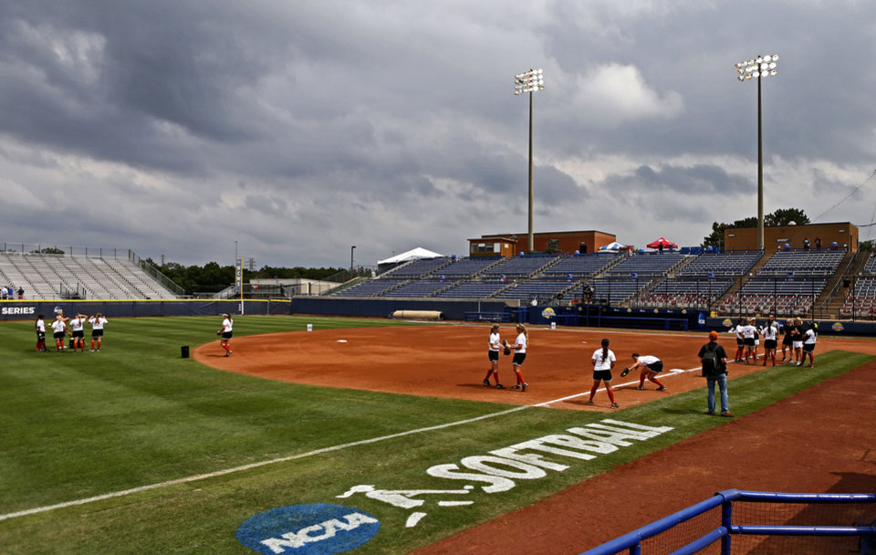 Photo - COLLEGE SOFTBALL: Storm clouds form as the University of Texas softball team practices the day before the opening game of the Women's College World Series at ASA Hall of Fame Stadium in Oklahoma City, Wednesday, May 29, 2013. Photo by Bryan Terry, The Oklahoman