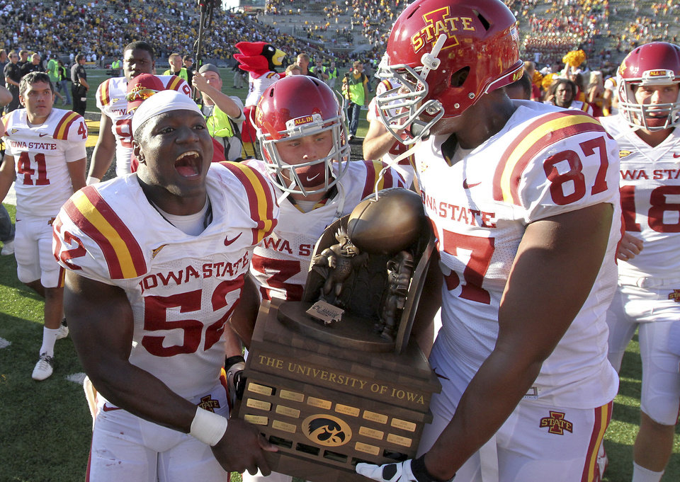Photo -   Iowa State players, from left, Jeremiah George, Jeff Woody and David Irving carry the Iowa Corn CyHawk Series trophy from the field after Iowa State defeated Iowa 9-6 in an NCAA college football game Saturday, Sept. 8, 2012, in Iowa City, Iowa. (AP Photo/Conrad Schmidt)