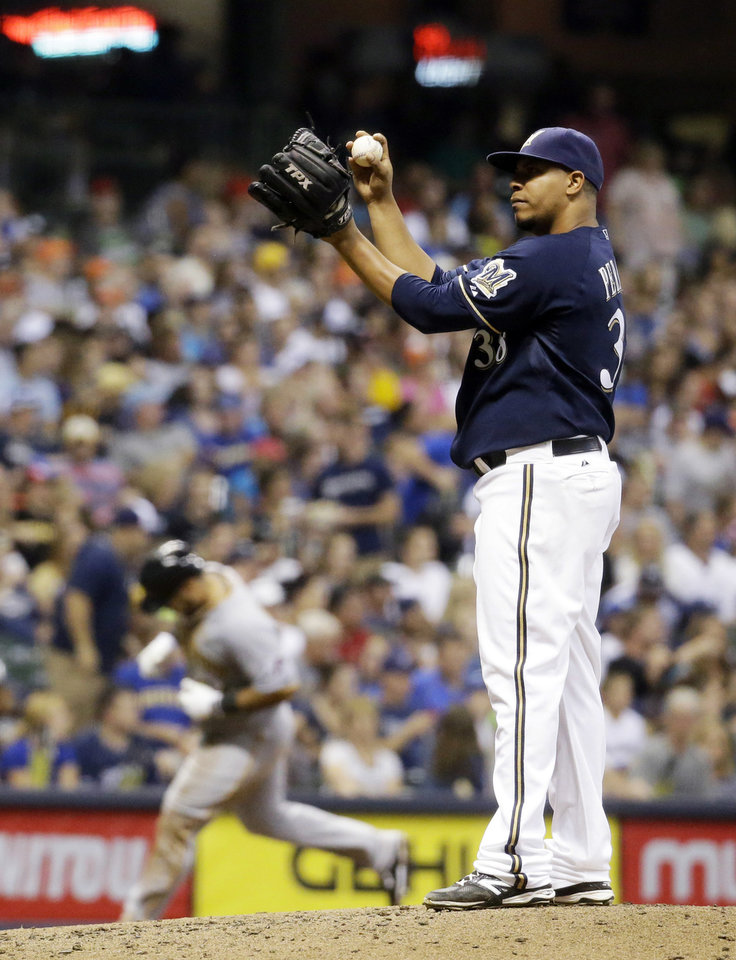Photo - Milwaukee Brewers starting pitcher Wily Peralta reacts as Pittsburgh Pirates' Russell Martin rounds the bases after Martin hit a three-run home run during the fifth inning of a baseball game Saturday, Aug. 23, 2014, in Milwaukee. (AP Photo/Morry Gash)