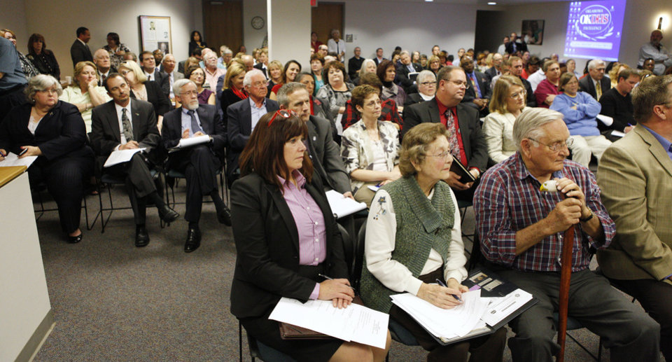 Photo - The crowd listens to commission members talk about closing the centers in Enid and Pauls Valley during Thursday's meeting. Photos by Paul B. Southerland, The Oklahoman