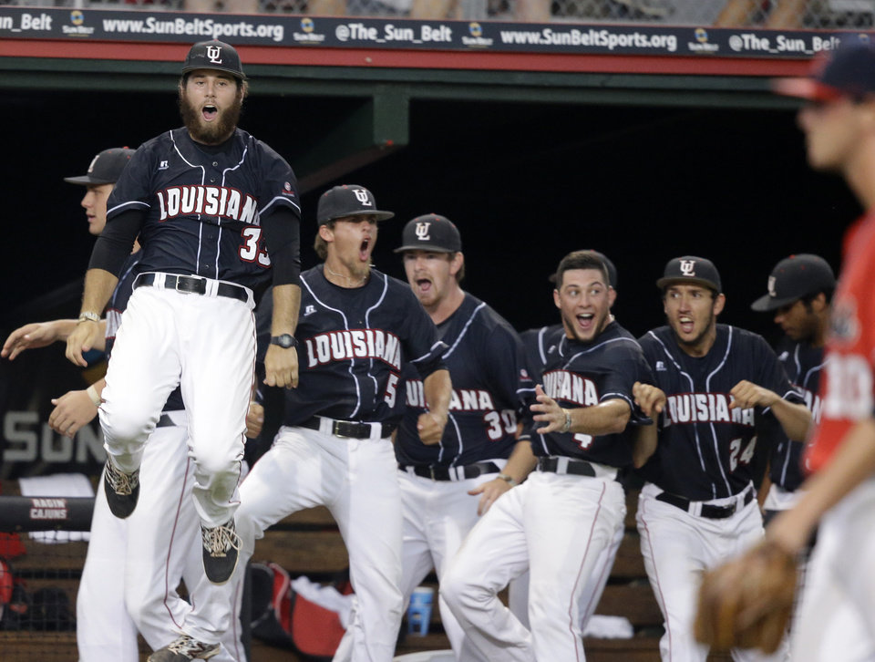 Photo - The Louisiana Lafayette bench reacts after Tyler Girouard's three run home run of Mississippi pitcher Chris Ellis, right, in the third inning of an NCAA college baseball tournament super regional game in Lafayette, La., Saturday, June 7, 2014. (AP Photo/Gerald Herbert)