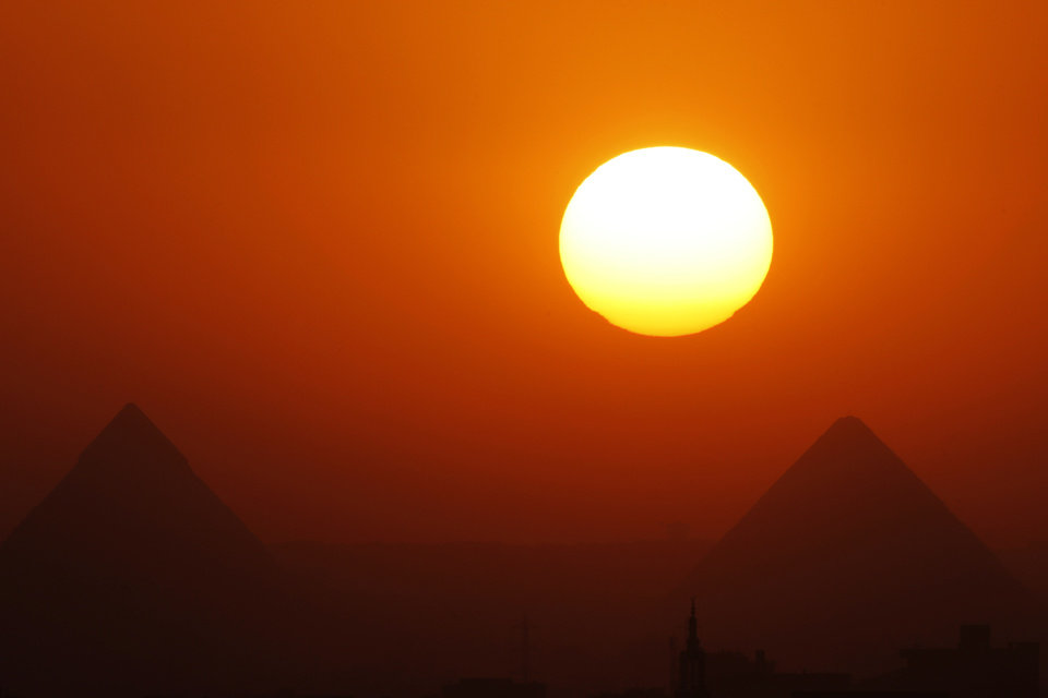 Photo - The sun sets behind the Great Pyramids in Giza, Egypt, Friday, April 26, 2013. Elsewhere, dozens of mostly masked protesters are hurling stones and firebombs in clashes with riot police at Egypt's presidential palace in a Cairo suburb. Protests have become a weekly routine in Egypt, as the country has plunged in turmoil during most of the past two years since 2011 uprising which ousted longtime president Hosni Mubarak out of power.  (AP Photo/Amr Nabil)