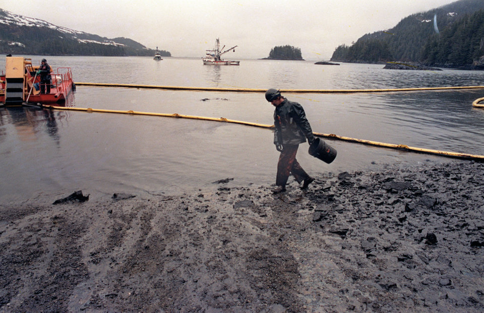 Photo - FILE - In this April 17, 1989, file photo, a worker makes his way across the polluted shore of Block Island,  Alaska, as efforts are underway to test techniques to clean up the oil spill of the tanker Exxon Valdez in Prince William Sound.  The worker periodically uses the bucket to scoop up oil washing back onto shore from the containment booms.  Nearly 25 years after the Exxon Valdez oil spill off the coast of Alaska, some damage heals, some effects linger in Prince William Sound. (AP Photo/John Gaps III, File)