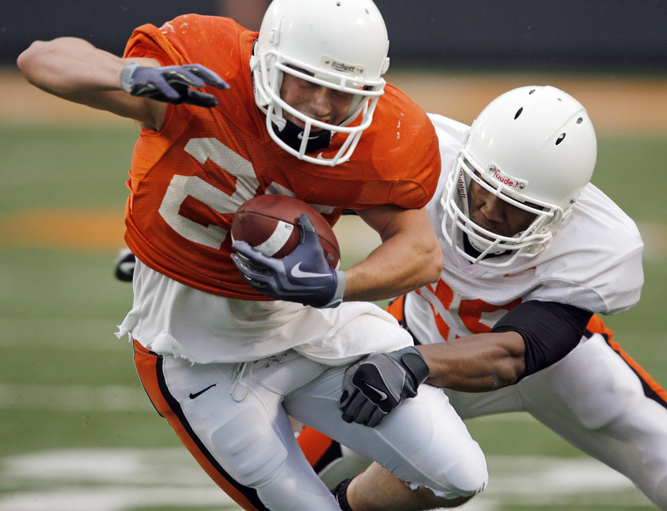 Photo - OKLAHOMA STATE UNIVERSITY / OSU / COLLEGE FOOTBALL / ORANGE AND WHITE SPRING GAME: OSU's Josh Cooper (25) tries to get away from the defense of Joe Mitchell (29) during the Oklahoma State Orange and White spring football game at Boone Pickens Stadium in Stillwater, Okla., Saturday, April 17, 2010. Photo by Nate Billings, The Oklahoman ORG XMIT: KOD