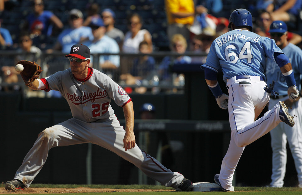 Photo - Washington Nationals first baseman Adam LaRoche (25) gets the throw as Kansas City Royals'  Emilio Bonifacio (64) runs to first base in the eighth inning of a baseball game at Kauffman Stadium in Kansas City, Mo., Sunday, Aug. 25, 2013. Bonifacio was called out on the play. (AP Photo/Colin E. Braley)