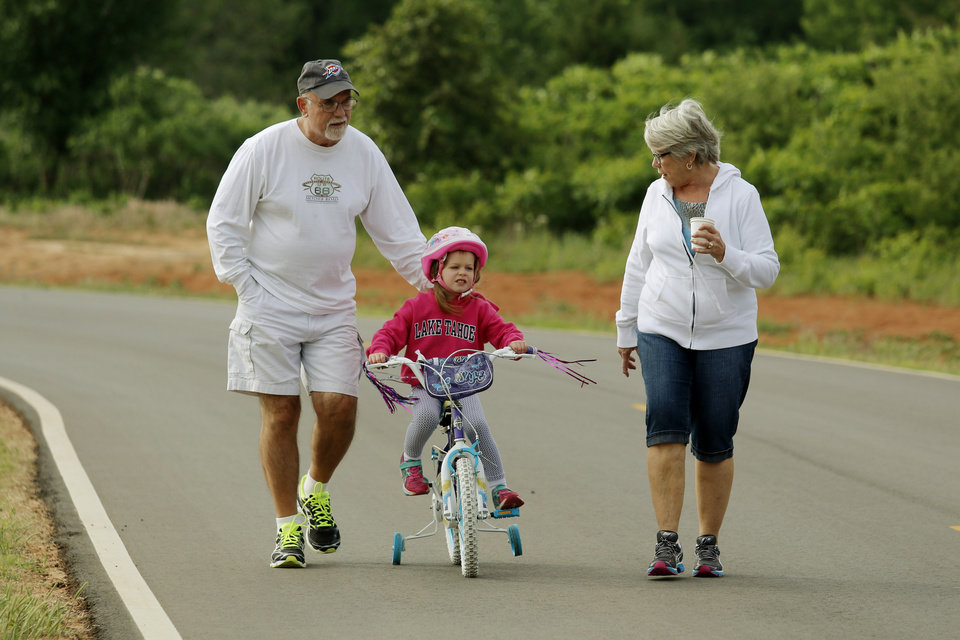 Photo - Jim and Susie Comer escort their grand daughter Abby, 4, on the first Edmond Family Bike Ride to encourage families and children to ride their bicycles for fitness and fun takes off at J.L. Mitch Park Saturday, May 17, 2014. Photo by Doug Hoke, The Oklahoman