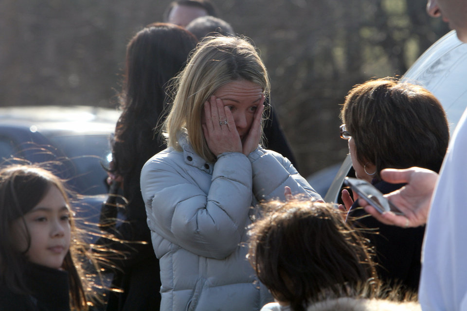 Photo - A woman weeps as she arrives to pick up her children at the Sandy Hook Elementary School in Newtown, Conn. where authorities say a gunman opened fire, leaving 27 people dead, including 20 children, Friday, Dec. 14, 2012. (AP Photo/The Journal News, Frank Becerra Jr.) MANDATORY CREDIT, NYC OUT, NO SALES, TV OUT, NEWSDAY OUT; MAGS OUT ORG XMIT: NYWHI106