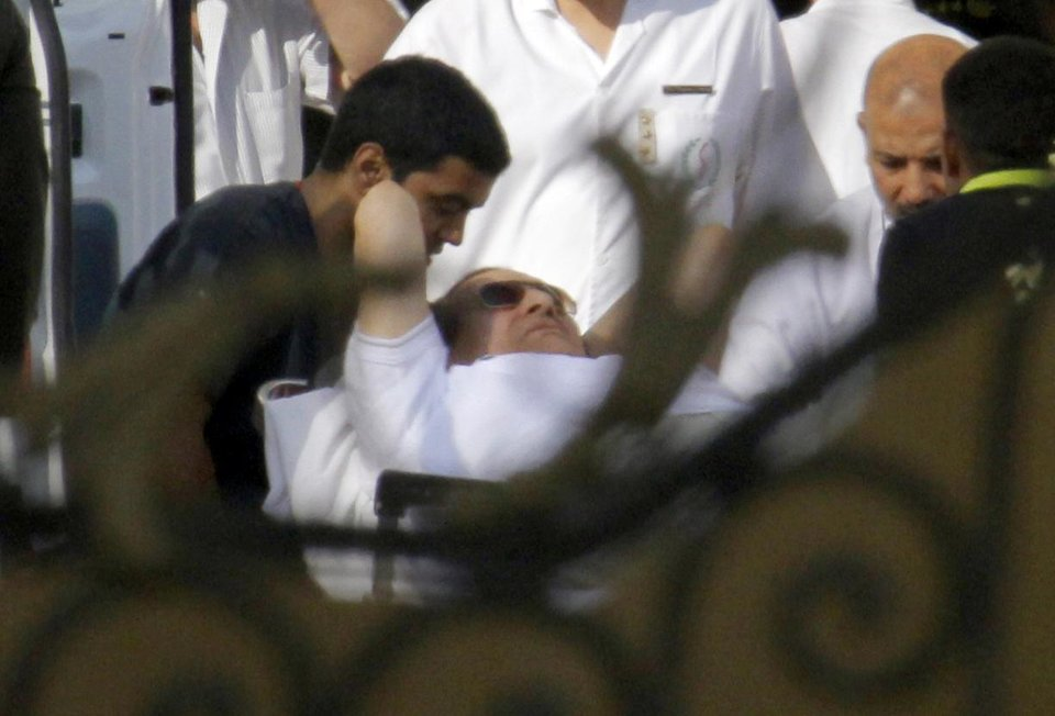 Photo - Egyptian medics escort former Egyptian President Hosni Mubarak, 85, into an ambulance after he was flown by a helicopter ambulance to the Maadi Military Hospital from Torah prison in, Cairo, Egypt, Thursday, Aug. 22, 2013. Egypt's ousted leader Hosni Mubarak has been released from jail and taken to military hospital in Cairo. (AP Photo/Amr Nabil)