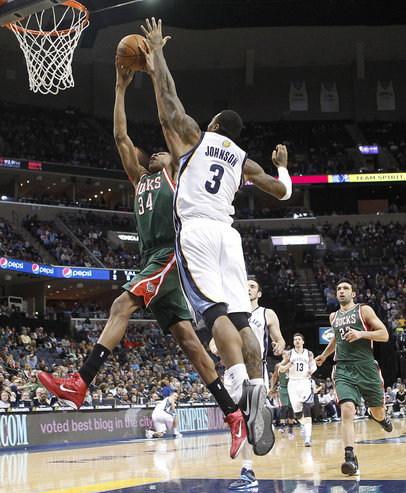 Photo - Milwaukee Bucks guard Giannis Antetokounmpo (34) goes to the basket against Memphis Grizzlies forward James Johnson (3) in the first half of an NBA basketball game on Saturday, Feb. 1, 2014, in Memphis, Tenn. (AP Photo/Lance Murphey)