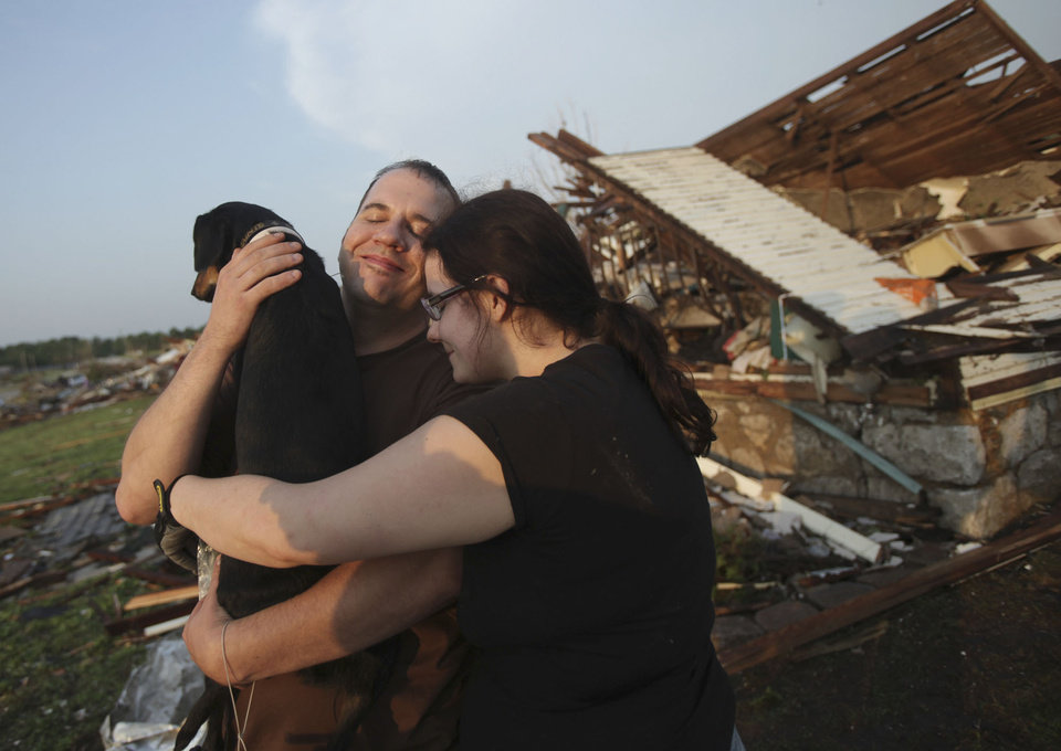 Photo - Maggie Kelley and her husband, Trey Adams hug their dog, Saint, after finding him amid the rubble of her home in Joplin, Mo. Monday, May 23, 2011.  The two are Hurricane Katrina evacuees. Joplin was leveled by a tornado that destroyed nearly 30 percent of the town on Sunday afternoon. The twister cut a six-mile path through the city. (AP Photo/Tulsa World, Adam Wisneski) ORG XMIT: OKTUL107