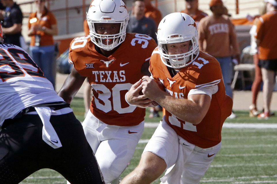 Photo -  Texas quarterback Sam Ehlinger runs during the first half of the game Saturday. [AP PHOTO]