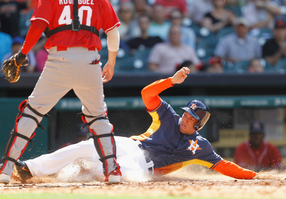 Photo - Houston's George Springer slides safely at home in the seventh inning in front of  Rojos del Aguila de Veracruz's catcher Leonardo Rodriguez during a spring exhibition baseball game on Sunday, March 30, 2014, in Houston. Houston won 6-1. (AP Photo/Bob Levey)