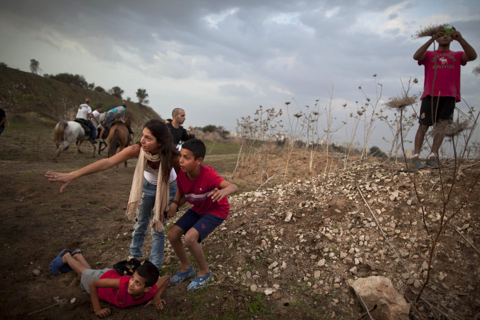 Israelis take cover as an air raid siren warns of incoming rockets from Gaza, next to an Iron Dome defense system in Tel Aviv, Saturday, Nov. 17, 2012. Israel bombarded the Hamas-ruled Gaza Strip with nearly 200 airstrikes early Saturday, the military said, widening a blistering assault on Gaza rocket operations to include the prime minister\'s headquarters, a police compound and a vast network of smuggling tunnels. (AP Photo/Oded Balilty)