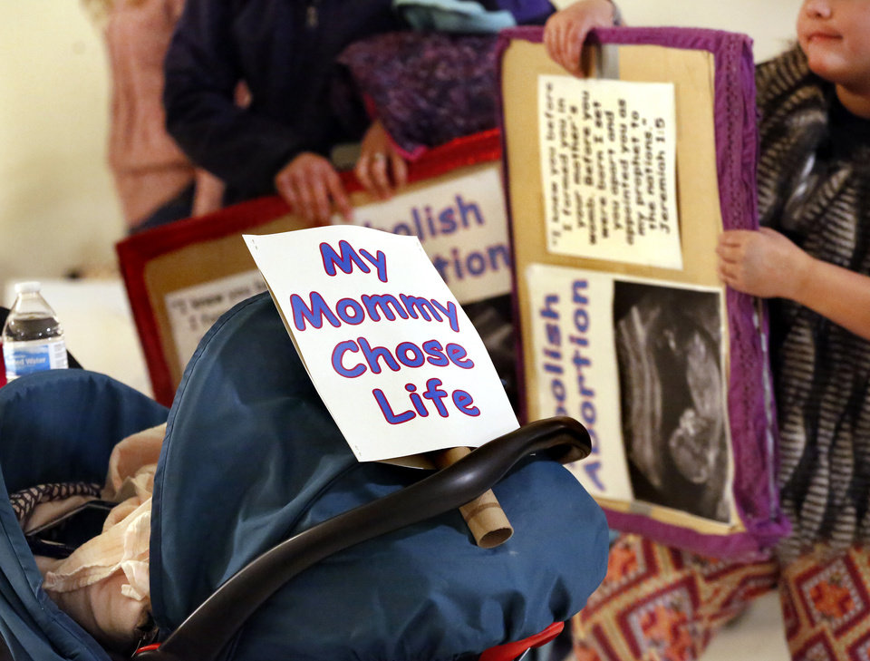 Photo - A vocal crowd of about 400 pro-life activists carried signs condemning abortion, calling it an act of murder,  and cheered a lengthy slate of speakers who urged the group to stand and fight  for the repeal of legalized abortion in America during a rally on the first floor of the state Capitol Tuesday morning, Feb. 12, 2019.  Oklahomans opposing abortion have expressed a new energy with a Trump presidency and the belief the U.S. Supreme Court has shifted. Ultimately, their goal, through legal channels, is  an overturning of landmark Supreme Court decision, Roe v. Wade. Currently, there are several anti-abortion bills that activists are looking to promote. Senate Bill 13 would make abortion a felony homicide and many who gathered at the Capitol said they wanted lawmakers to support the bill, even if it resulted in a legal challenge.