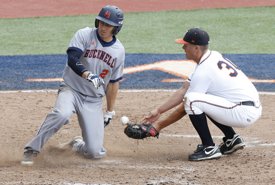 Photo - Bucknell outfielder Brett Smith (2) scores a run as Virginia pitcher Connor Jones (30) bobbles the ball in the eighth inning during an NCAA college regional tournament baseball game in Charlottesville, Va., Friday, May 30, 2014. Virginia won the game 10-1. Smith scored on a wild pitch.  (AP Photo/Steve Helber)