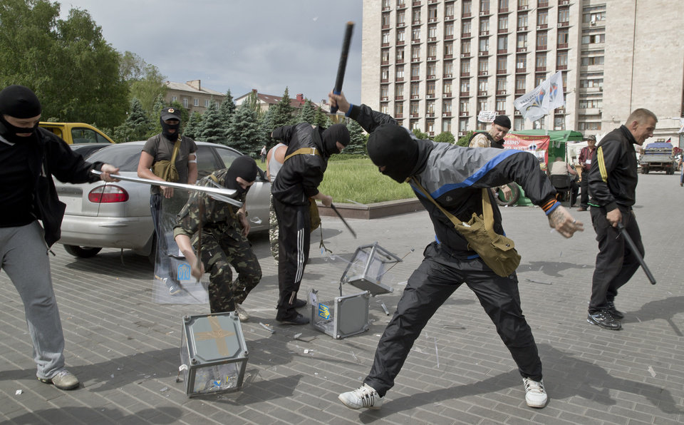 Photo - Pro-Russian militants smash ballot boxes in front of the seized regional administration building in Donetsk, Ukraine, Sunday, May 25, 2014. Ukraine's critical presidential election got underway Sunday under the wary scrutiny of a world eager for stability in a country rocked by a deadly uprising in the east. While there were no immediate reports of violence, pro-Russia insurgents were trying to block voting by snatching ballot boxes and patrolling polling stations.(AP Photo/Vadim Ghirda)