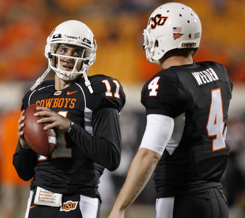 Photo - OSU's Zac Robsinson, left, and Brandon Weeden talk before the college football game between Oklahoma State University (OSU) and the University of Colorado (CU) at Boone Pickens Stadium in Stillwater, Okla., Thursday, Nov. 19, 2009. Photo by Nate Billings, The Oklahoman