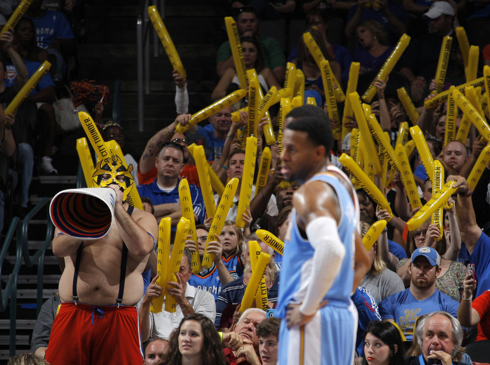 Photo - Oklahoma City fans try to distract a free-throw attempt by Denver during the NBA preseason basketball game between the Oklahoma City Thunder and the Denver Nuggets at the Chesapeake Energy Arena, Sunday, Oct. 21, 2012. Photo by Garett Fisbeck, The Oklahoman