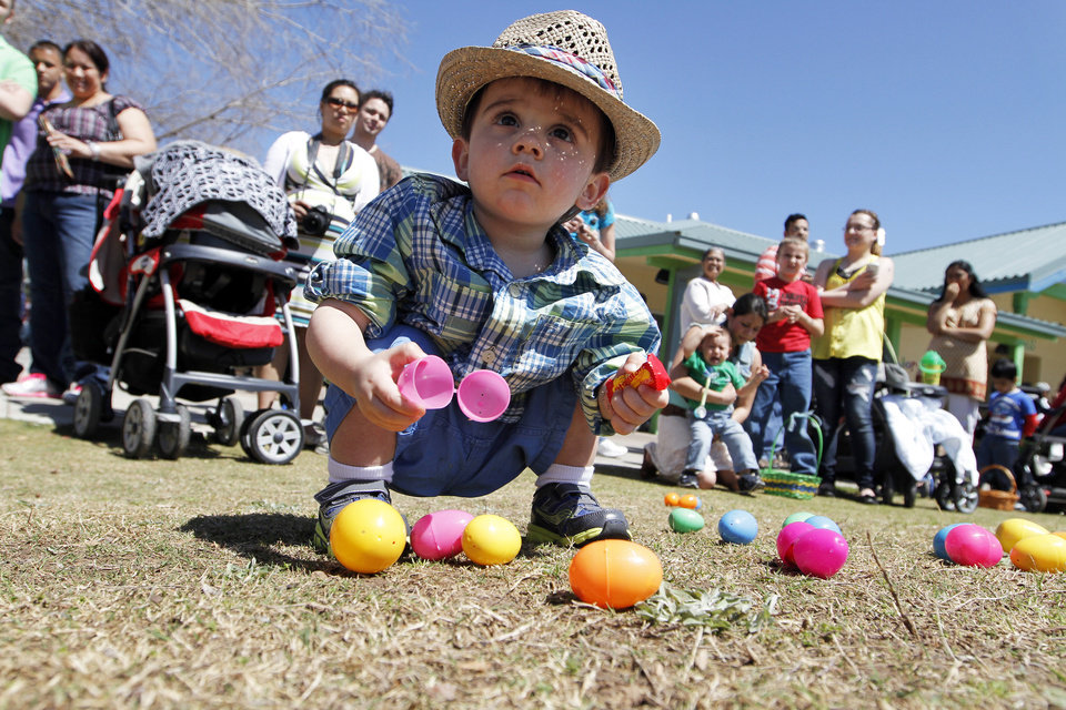 Photo - EASTER ACTIVITIES / CHILD / CHILDREN / KIDS: Caden Abrams, 17 months, of Oklahoma City, looks at Easter Eggs during HOPabaloo at the Oklahoma City Zoo, Sunday, March 31, 2013.  PHOTO BY GARETT FISBECK, FOR THE OKLAHOMAN        ORG XMIT: 1303312222051033