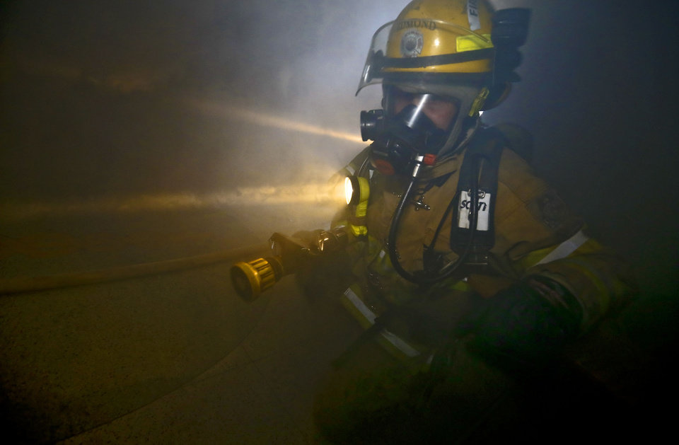 An Edmond firefighter makes his way through a smoke-filled building in downtown as part of a self-contained breathing apparatus drill. PHOTOS BY CHRIS LANDSBERGER, THE OKLAHOMAN