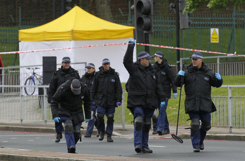 Photo - Police search team leave the scene of a terror attack in Woolwich, southeast London, Thursday, May 23, 2013. A member of armed forces was attacked and killed by two men on Wednesday. (AP Photo/Sang Tan)
