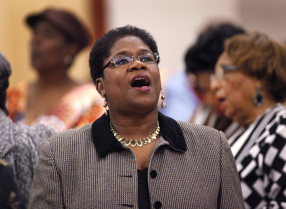 Photo - Debra Johnson joins others in the audience in singing the national Negro anthem near the end of the 16th annual Midwest City Dr. Martin Luther King, Jr. Prayer Breakfast inside the Reed Conference Center Monday morning, Jan. 21, 2013. Johnson is youth minister at St. John Missionary Baptist Church. The theme of this year's event is